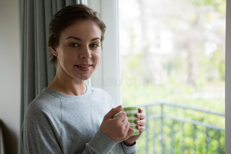Smiling woman having cup of coffee at home stock image