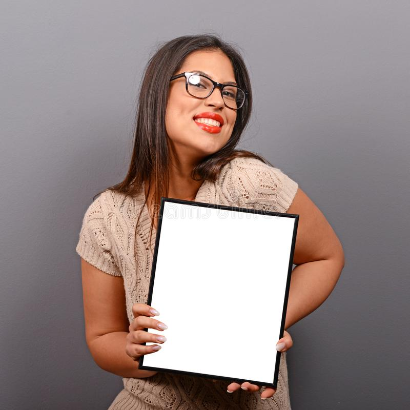 Portrait of smiling woman holding blank photo frame against gray background royalty free stock images