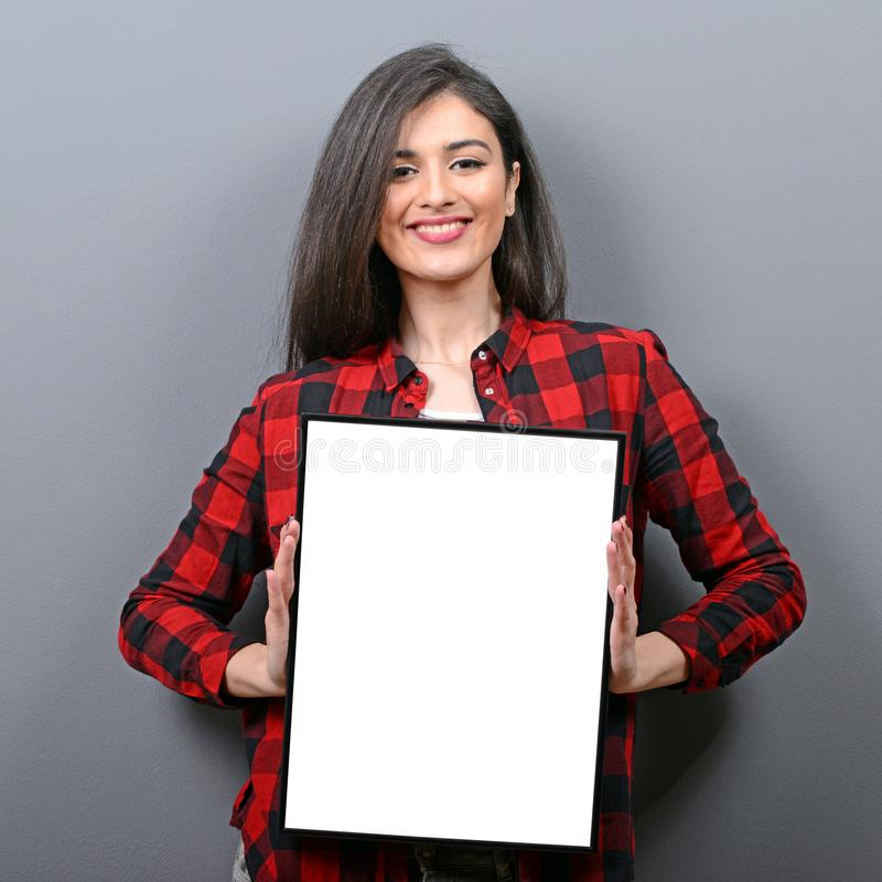 Portrait of smiling woman holding blank sign board.Studio portrait of young woman with sign card against gray background stock photo