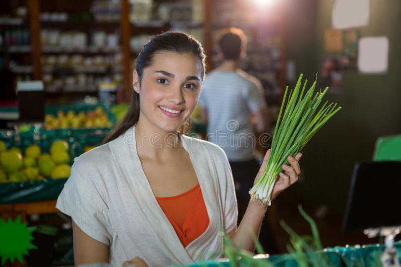 Portrait of smiling woman holding bunch of scallions in organic section. Portrait of smiling women holding bunch of scallions in organic section of supermarket stock image