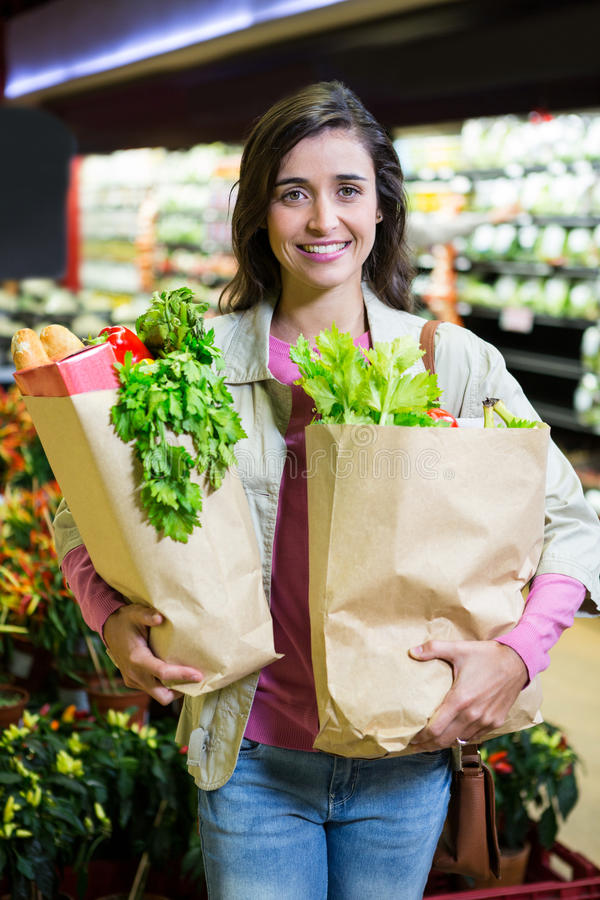 Portrait of smiling woman holding a grocery bag in organic section. Of supermarket royalty free stock photo