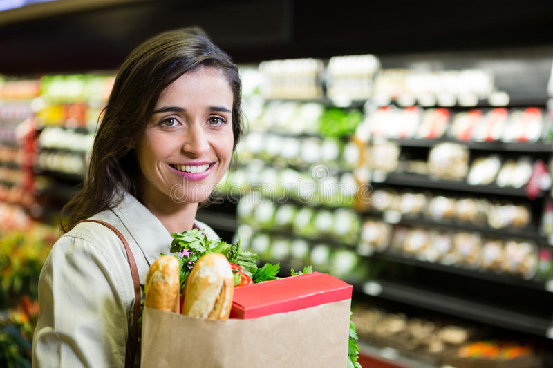Portrait of smiling woman holding a grocery bag in organic section. Of supermarket royalty free stock images