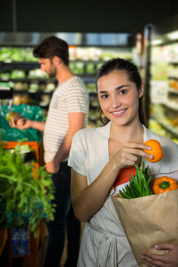 Portrait of smiling woman holding a grocery bag in organic section. Portrait of smiling women holding a grocery bag in organic section of supermarket stock image