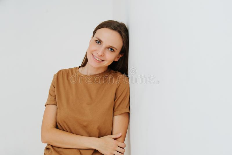 Portrait of a smiling woman, leaning on the wall, with one hand holding another royalty free stock photos