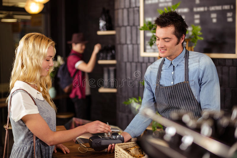 Portrait of a smiling woman paying with credit card stock photography
