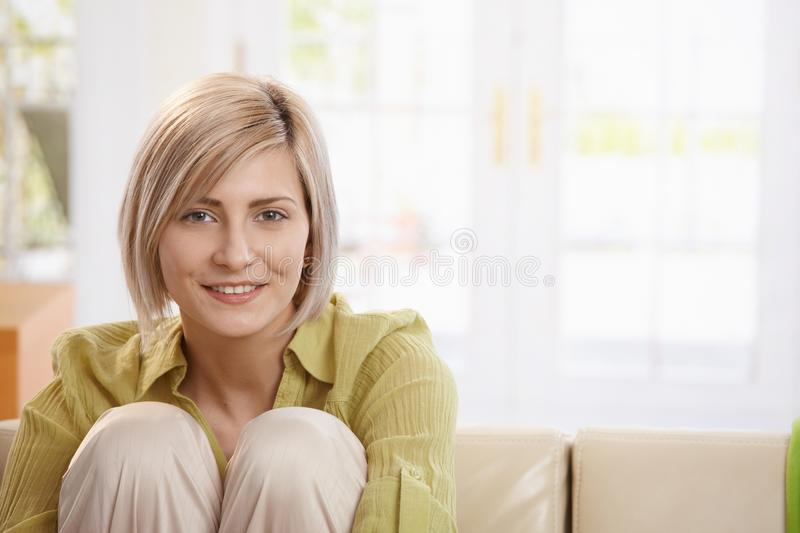 Portrait of smiling woman. Sitting with arms around knees in living room, looking at camera stock image