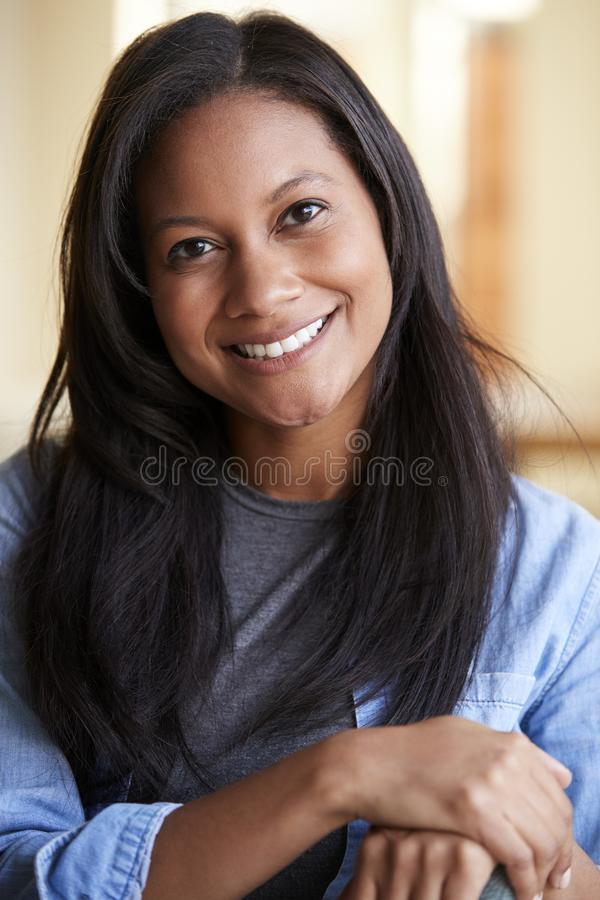 Portrait Of Smiling Woman Relaxing On Sofa At Home stock photo