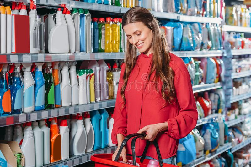 portrait of smiling woman with shopping basket royalty free stock image