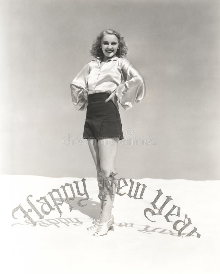 Portrait of smiling woman standing by Happy New Year sign royalty free stock image
