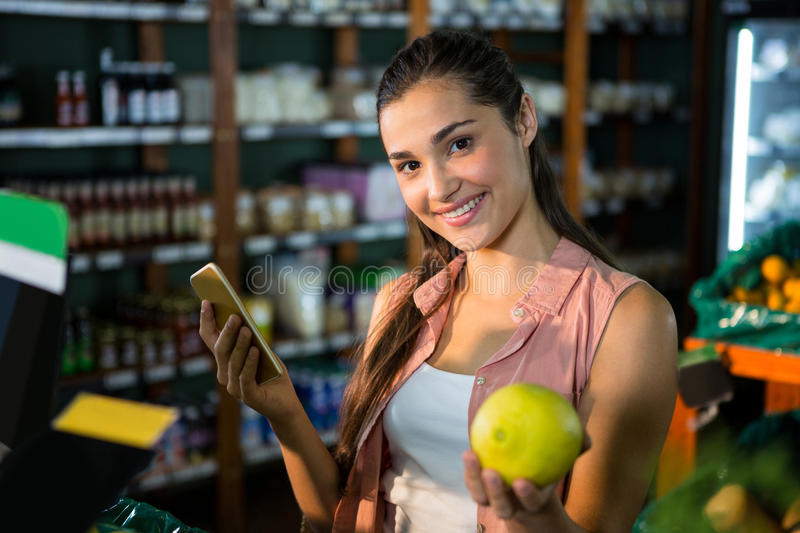 Portrait of smiling woman using her phone while buying fruits in organic section. Of supermarket royalty free stock photos