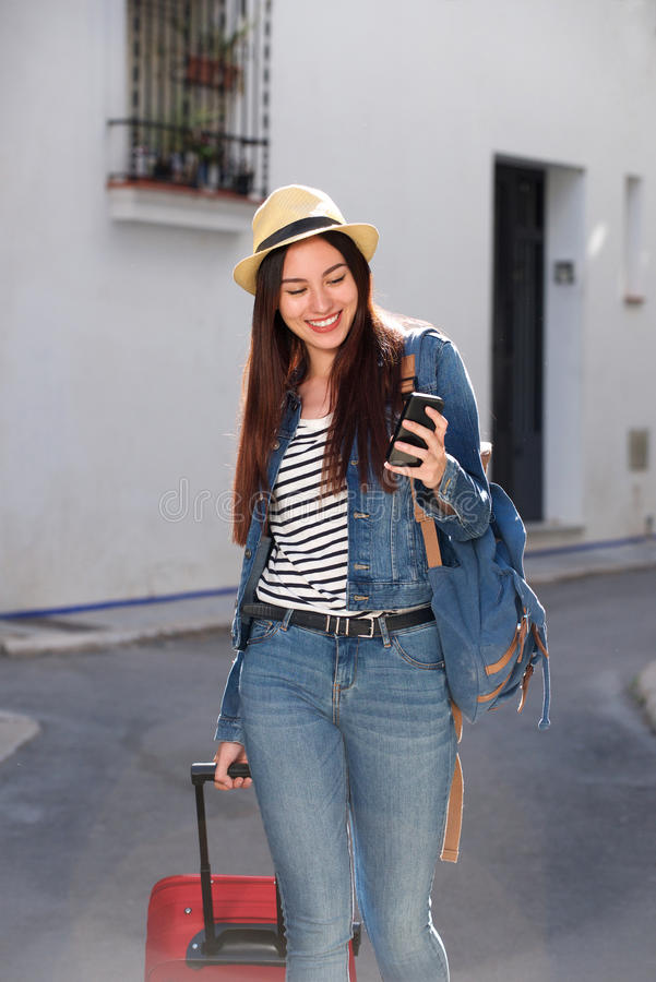 Smiling woman walking with luggage and holding cellphone outside stock photography