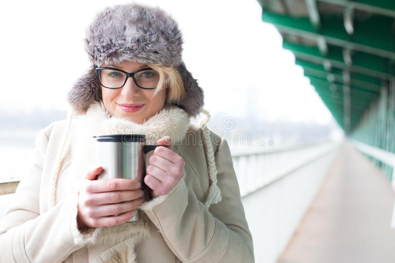 Portrait of smiling woman in warm clothing holding insulated drink container royalty free stock images