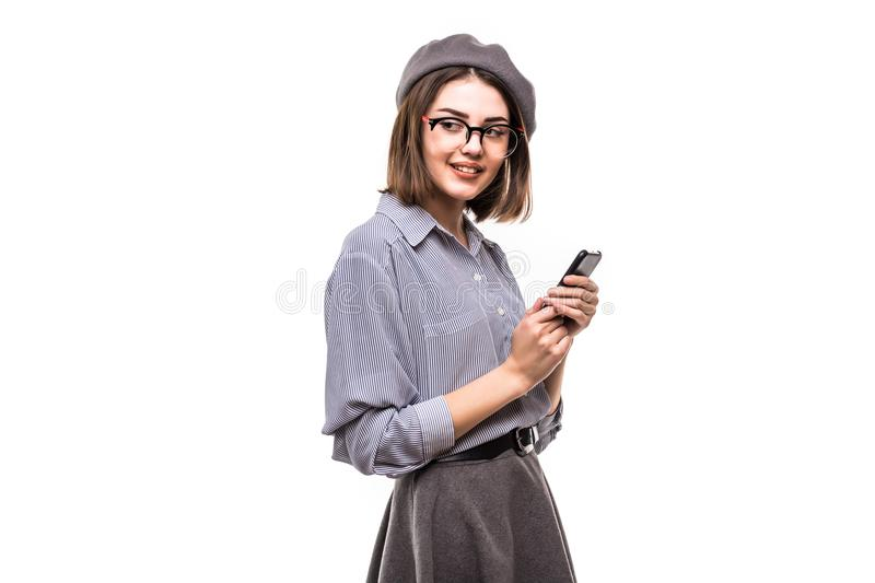 Portrait of a smiling woman wearing beret holding mobile phone over white background stock photo