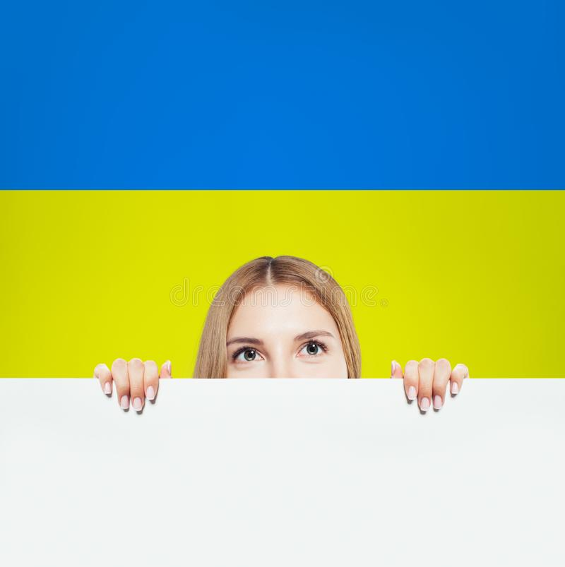 Portrait of smiling woman with white banner and Ukrainian flag stock image