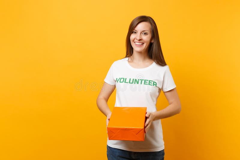Portrait of smiling woman in white t-shirt with written inscription green title volunteer hold orange cardboard box royalty free stock photography
