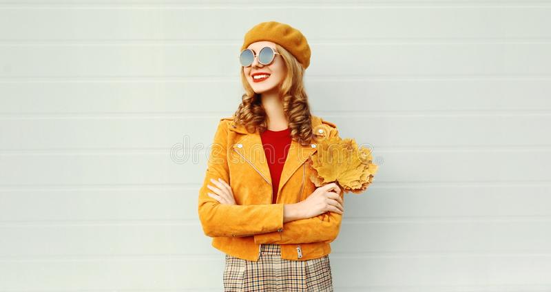 Portrait smiling woman with yellow maple leaves wearing orange french beret on city street over gray wall royalty free stock photo