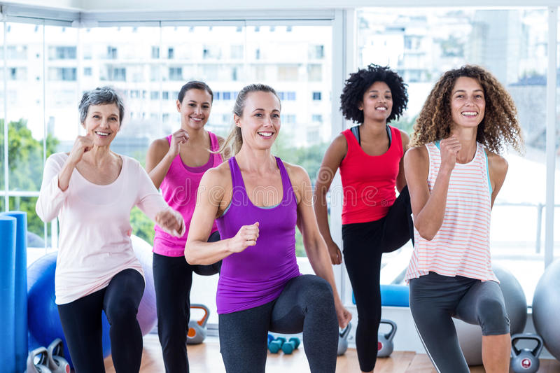 Portrait of smiling women exercising with clasped hands. In fitness studio stock image