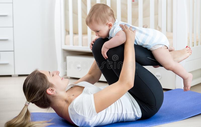 Portrait of smiling young woman practising yoga and fitness with her baby boy royalty free stock photography