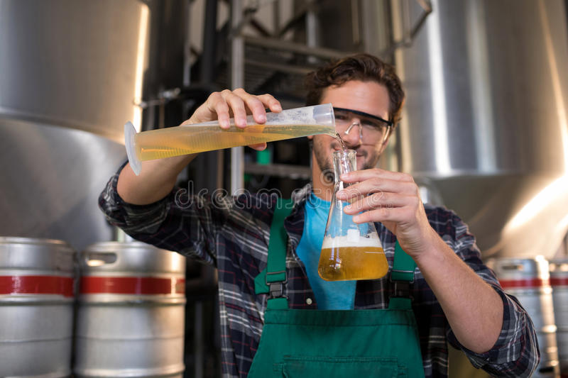Portrait of smiling worker pouring beer in beaker. At factory stock photo