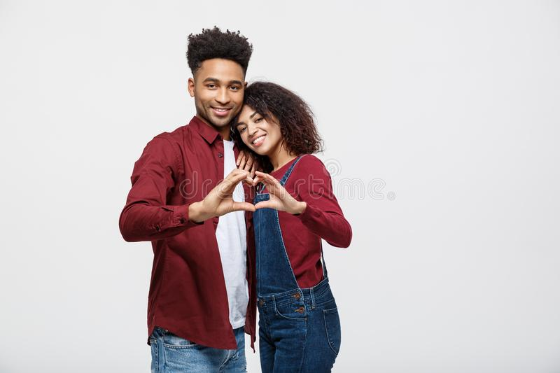 Portrait of a smiling young african couple dressed in casual clothes hugging and showing heart gesture with fingers. Isolated over white background stock images