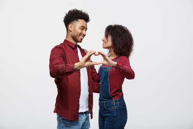 Portrait of a smiling young african couple dressed in casual clothes hugging and showing heart gesture with fingers. Isolated over white background royalty free stock photography