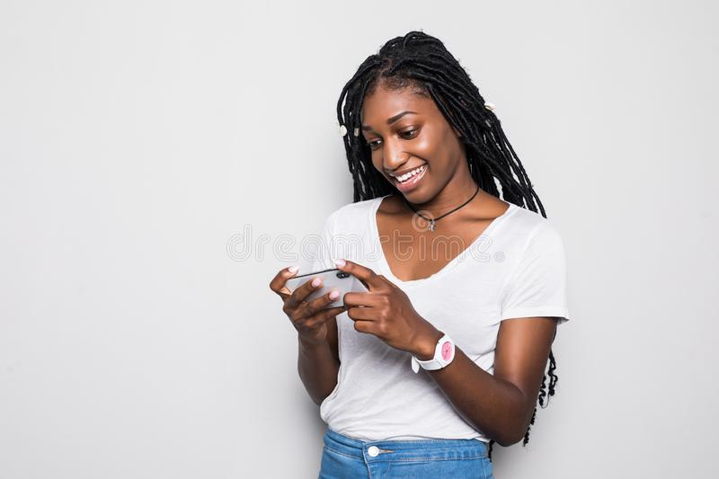 Portrait of a smiling young african woman playing games on mobile phone isolated over white background stock photography