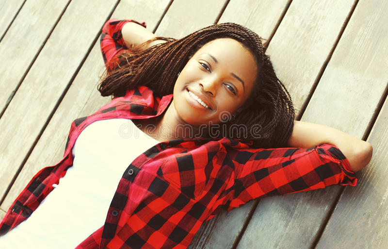 Portrait smiling young african woman relaxed on a wooden floor with hands behind head, wearing a red checkered shirt stock photos