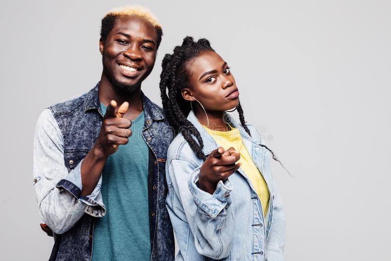 Portrait of a smiling young afro american couple standing and pointing at camera isolated over white background stock photo