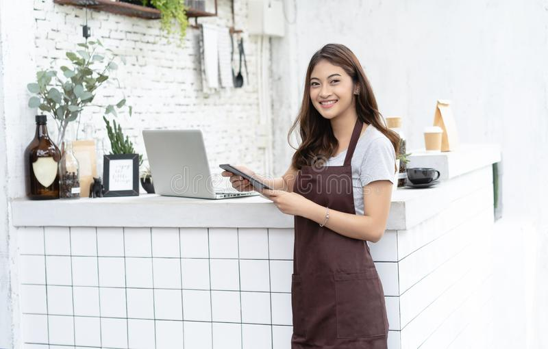 Portrait of a smiling young Asian barista in apron smiling using tablet and looking away on beside coffee machine in counter. royalty free stock images