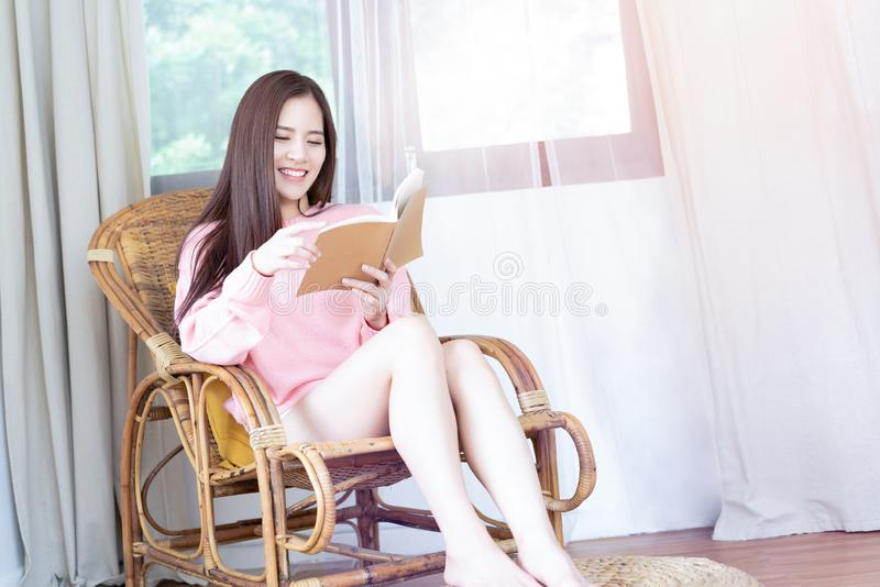 Portrait of smiling young Asian woman reading book while on vintage chair of window in her living room. Relax time and Lifestyle stock photos