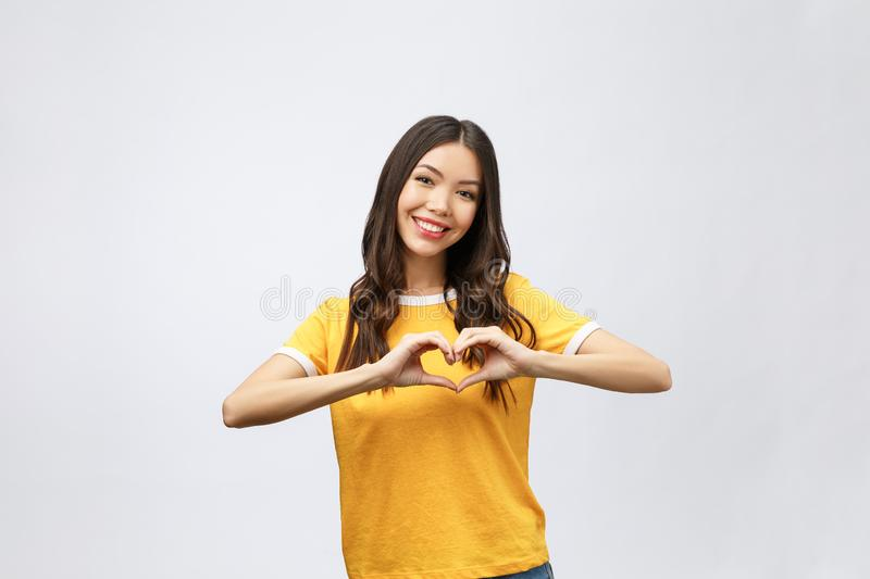 Portrait of a smiling young asian woman showing heart gesture with two hands and looking at camera isolated over white. Background royalty free stock images