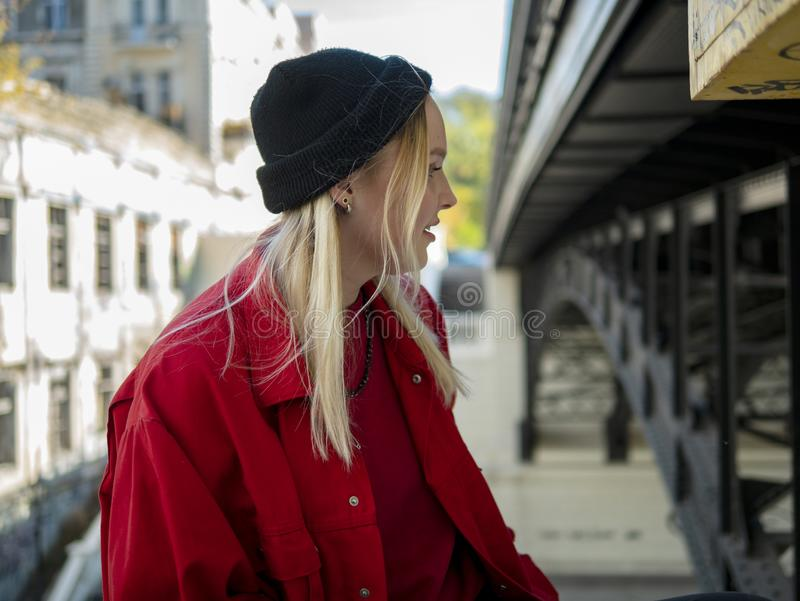 Portrait of a smiling young attractive girl in a red jacket and knitted black jacket under the bridge stock photo