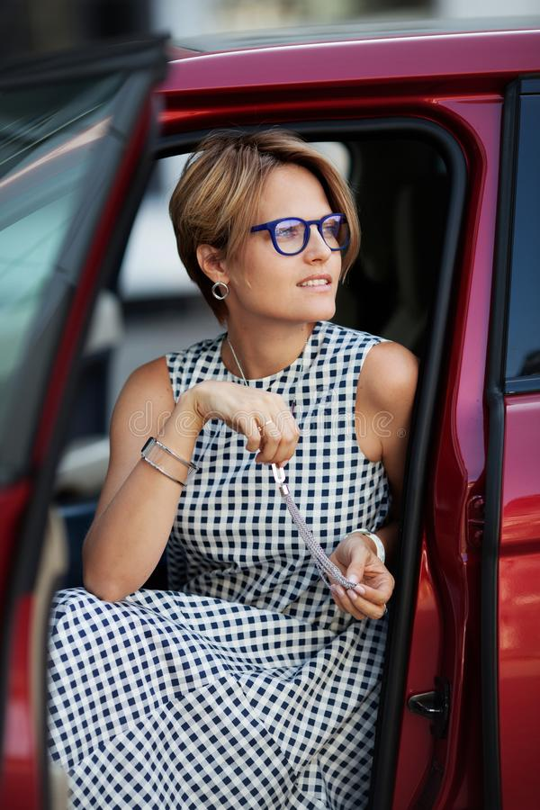 Portrait of smiling young beautiful woman sitting in the car stock photo