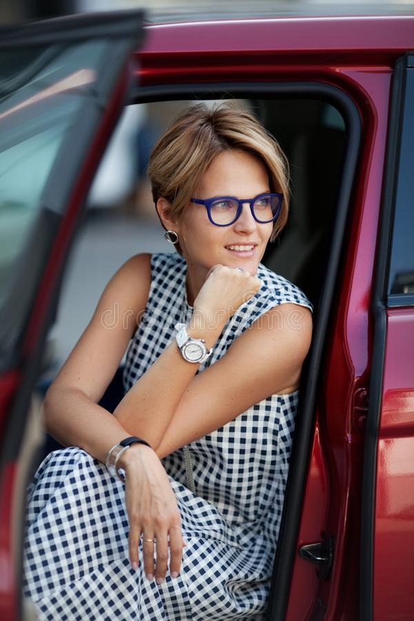 Portrait of smiling young beautiful woman sitting in the car stock photos