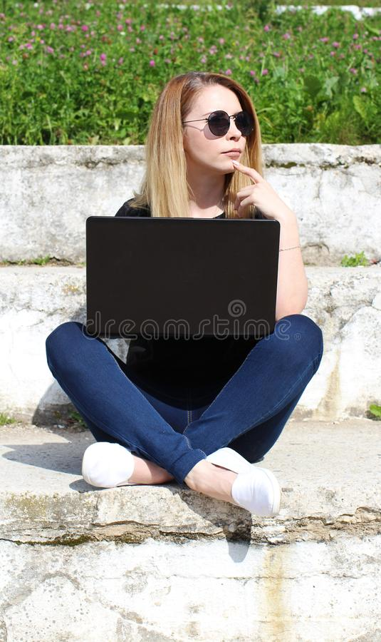 Portrait of a smiling young blonde girl holding laptop royalty free stock images