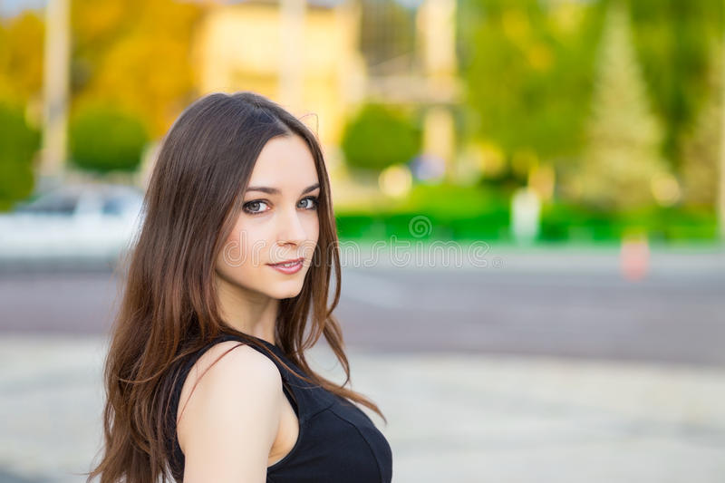 Portrait of smiling young brunette. Posing outdoors stock images
