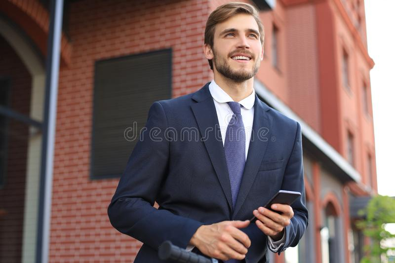Portrait of a smiling young business man dressed in suit talking on mobile while standing with bicycle outdoors. stock photo