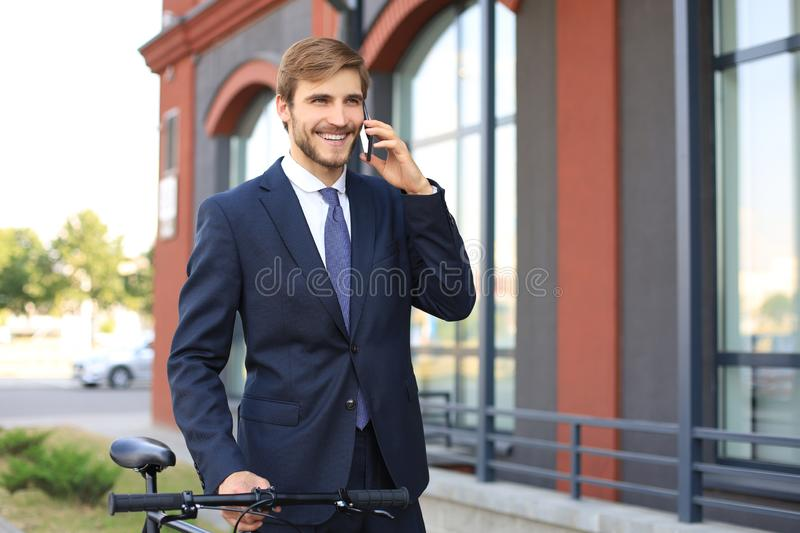 Portrait of a smiling young business man dressed in suit talking on mobile while standing with bicycle outdoors. stock images