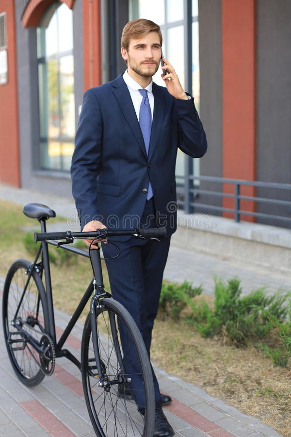 Portrait of a smiling young business man dressed in suit talking on mobile while standing with bicycle outdoors. royalty free stock photo