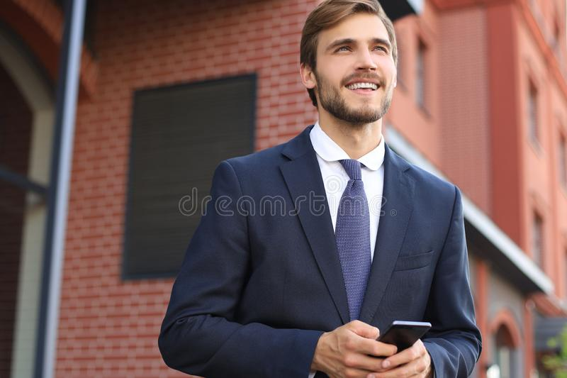 Portrait of a smiling young business man dressed in suit talking on mobile standing outdoors. stock images