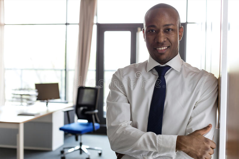 Portrait of smiling young businessman with arms crossed leaning on cupboard in office royalty free stock photography