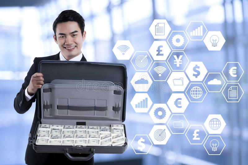Portrait of smiling young businessman holding a briefcase with d stock photos