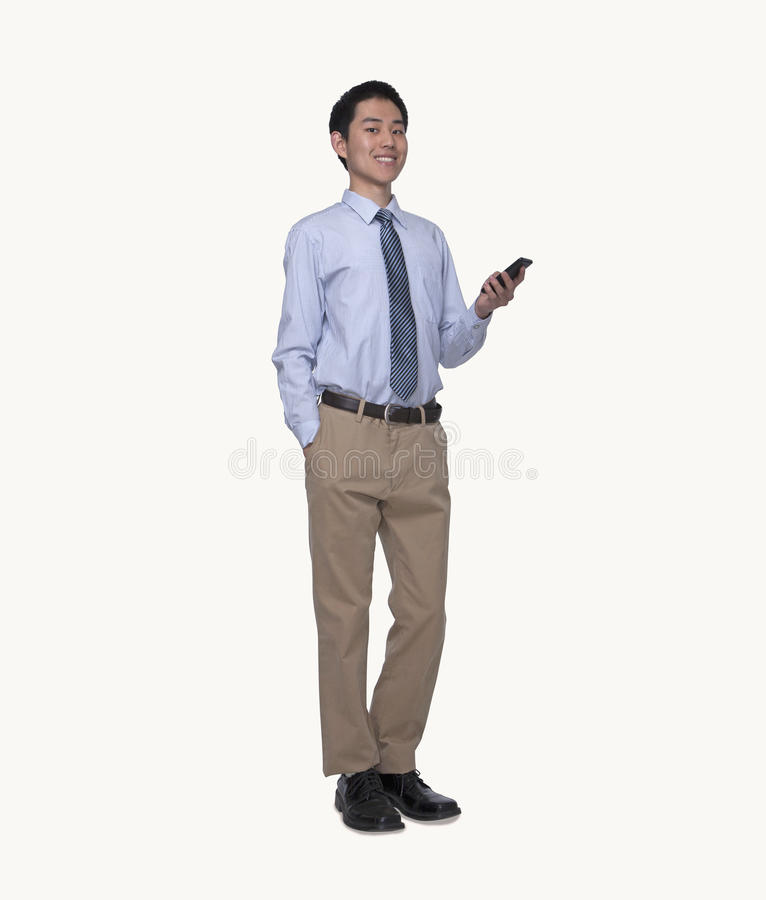 Portrait of smiling young businessman using his phone, full length, studio shot royalty free stock images