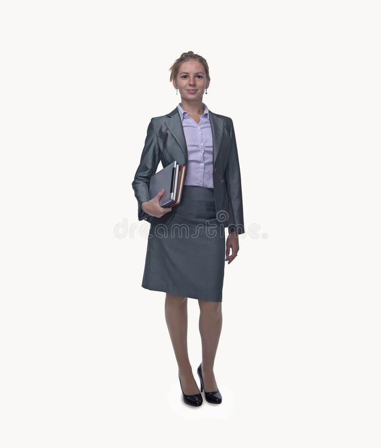 Portrait of smiling young businesswoman holding digital tablet and books, full length, studio shot royalty free stock photos