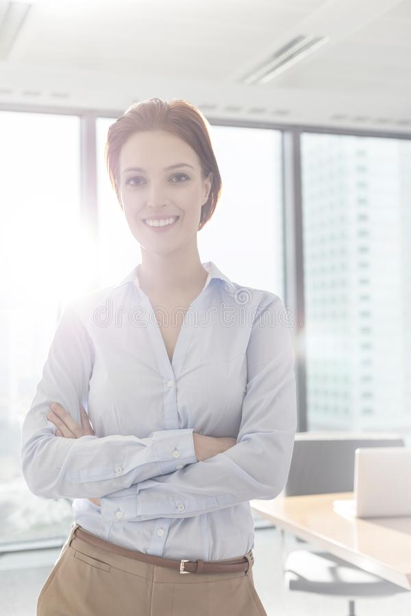 Portrait of smiling young businesswoman standing with arms crossed in boardroom at office stock image