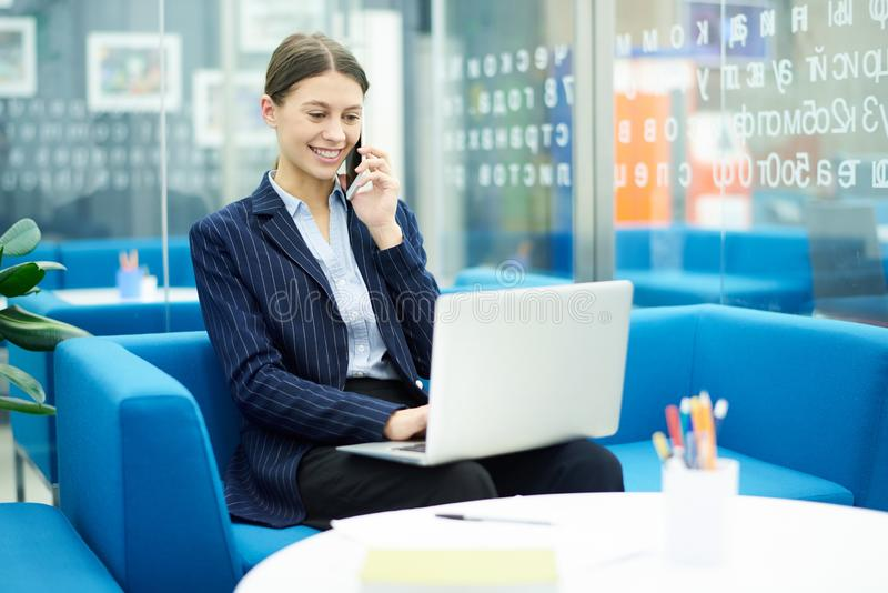 Young Businesswoman at Work. Portrait of smiling young businesswoman using laptop in office and speaking by phone during internship, copy space royalty free stock photography