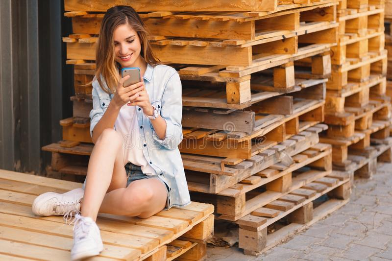 Portrait of a smiling young casual pretty woman looking at mobile phone stock photo