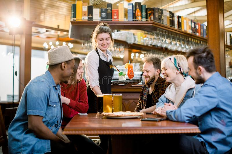 Portrait of smiling young diverse friends in indoors restaurant and smiling waitress with drinks and beer. Portrait of smiling young diverse friends in indoors stock photography