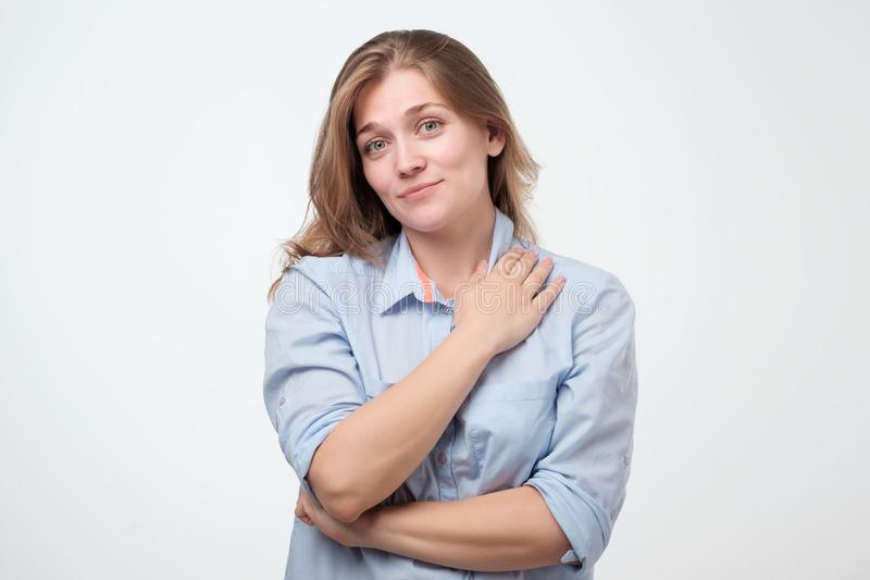 Portrait of a smiling young european woman standing with arms folded royalty free stock photo