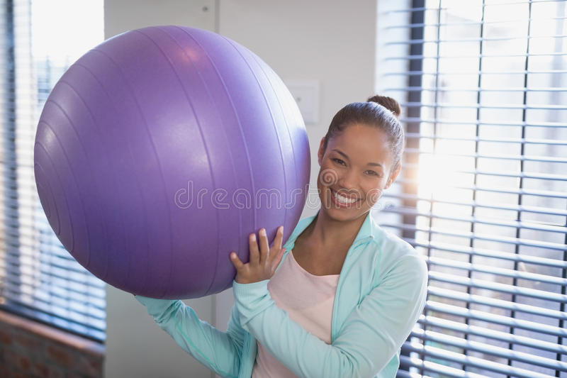 Portrait of smiling young female doctor holding purple exercise ball stock image